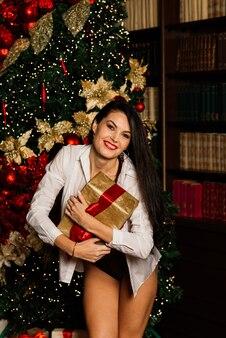 Natal, ano novo. linda mulher em lingerie, meias posando dentro de casa