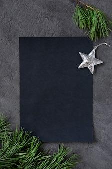 Natal, ano novo preto elegante background e em branco com um ramo de decorações de estrelas de abeto e prata. copie o espaço. vista do topo