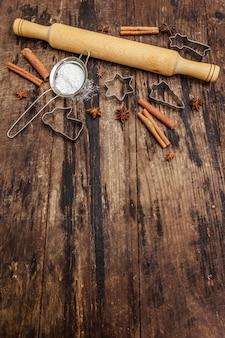 Natal assando, assar utensílios, temperos, cortadores de biscoitos - estrelas, anjo e abeto, peneira, açúcar em pó e um rolo. tábuas de madeira velhas