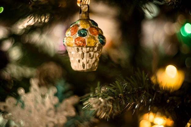 Natal atmosférico. um fragmento de close-up de uma árvore de natal com brinquedos, luzes de gerland