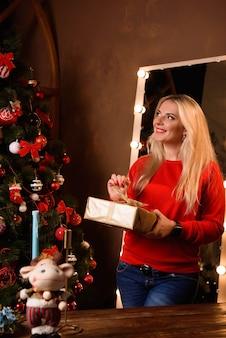 Natal. bela mulher sorridente. senhora sobre fundo de luzes de árvore de natal. feliz ano novo.