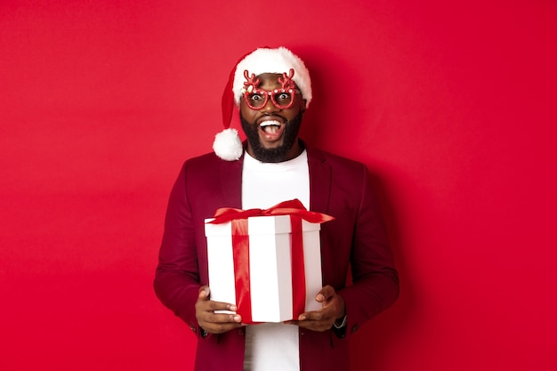 Natal. bonito homem afro-americano com óculos de festa e chapéu de papai noel segurando um presente de ano novo