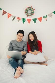 Natal. casal asiático usando tablet digital em casa, comemorando o ano novo.