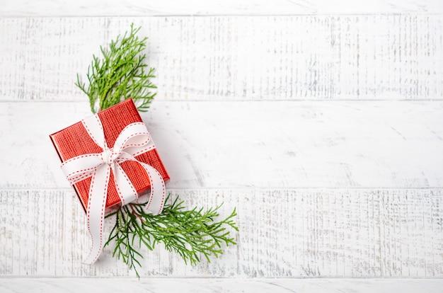 Natal com caixa de presente vermelha em um fundo branco de madeira. inverno festivo. vista superior, plana leigos, copyspace.
