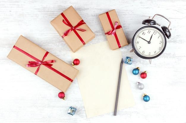 Natal com caixas de presente, despertador, bolas de decoração de natal e folha de papel na mesa de madeira branca