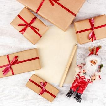 Natal com caixas de presente, papai noel e folha de papel na mesa de madeira branca