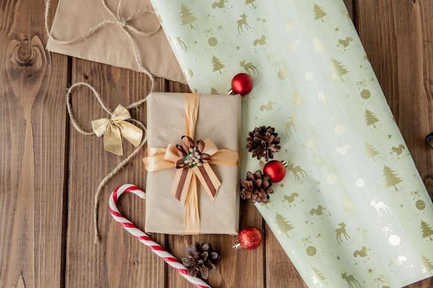 Natal com cones de natal e brinquedos, ramos de abeto, caixas de presente e decorações em um fundo de mesa de madeira