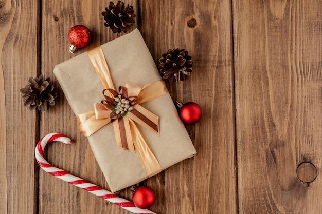 Natal com cones de natal e brinquedos, ramos de abeto, caixas de presente e decorações em uma mesa de madeira