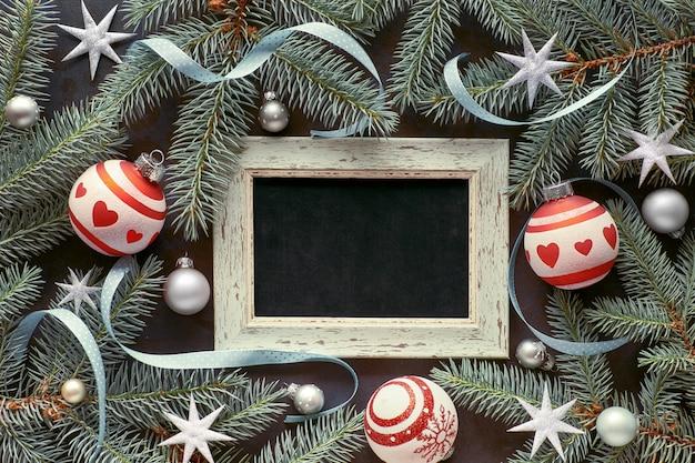 Natal com galhos de pinheiro, bugigangas em vermelho e prata, estrelas e fitas em torno do quadro-negro em branco