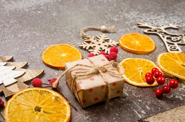Natal com presentes embrulhados em papel artesanal, brinquedos de madeira para árvore de natal, laranjas secas sobre fundo cinza claro. composição de ano novo ou véspera de inverno. conceito de época de natal. cartão de felicitações,