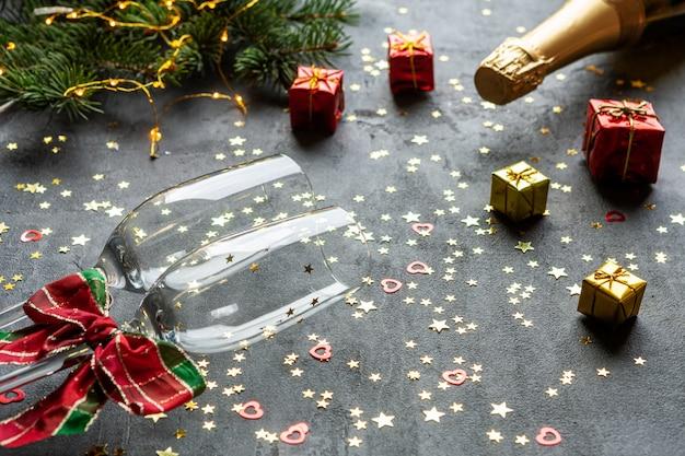 Natal, comemoração do ano novo - prato em forma de relógio, garrafas de champanhe, duas taças de champanhe e confetes com glitter dourado,