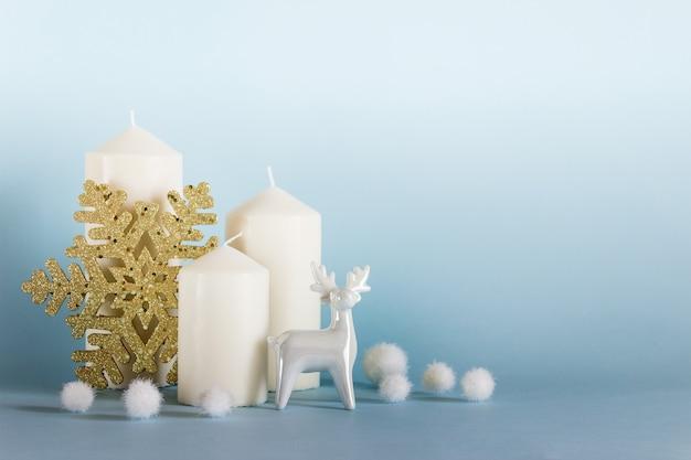 Natal, composição de ano novo com três velas brancas, renas de porcelana branca, floco de neve dourado e bolas brancas sobre fundo amarelo azul. foto com espaço em branco de cópia.