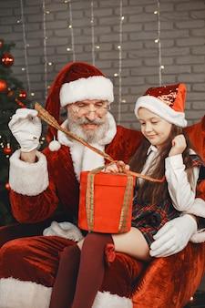 Natal, criança e presentes. papai noel trouxe presentes para a criança. menina alegre abraçando o papai noel.