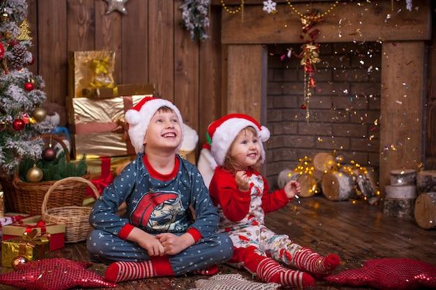 Natal. crianças de pijama admirando a serpentina dourada. eles admiram a magia do feriado. o natal é um tempo misterioso e maravilhoso