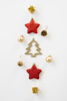 Natal criativo. layout de cartão liso leigos, vista superior. brinquedos de natal cor dourada e vermelha.
