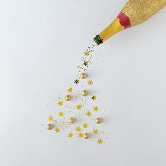 Natal criativo ou ano novo. garrafa de champanhe com árvore de natal de glitter dourados. conceito de layt plano mínimo.