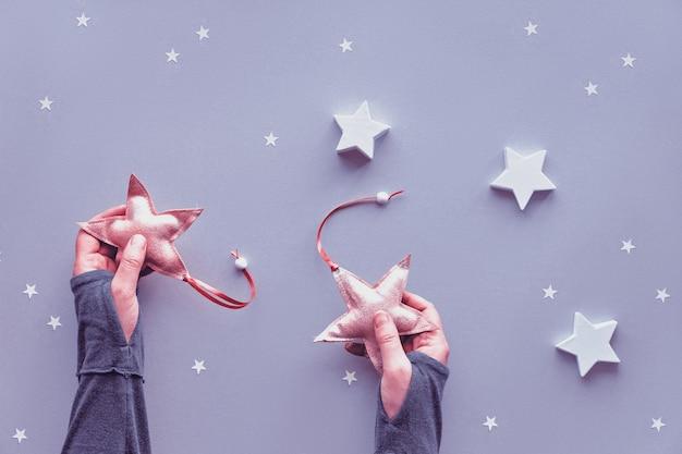 Natal criativo plana colocar em tons pastel, sobre fundo de papel cinza prata. mãos segurando estrelas têxteis macios, fundo cinza com estrelas de papel grandes e pequenos. fundo de inverno.