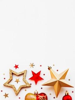 Natal e 2020 com enfeites, em forma de círculo. bolas douradas e vermelhas, estrelas, confetes e coração.