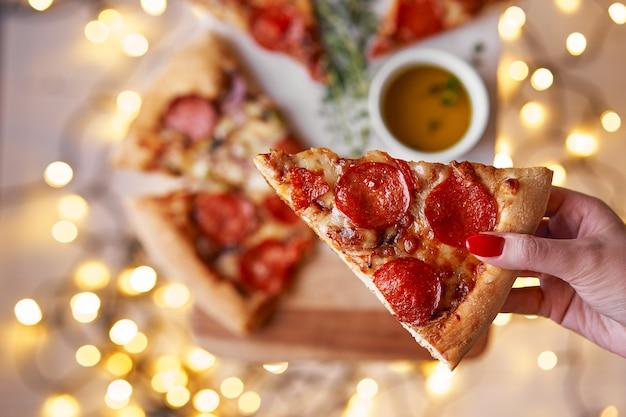 Natal e ano novo festivo. a mão da mulher toma a fatia de pepperoni italianos da pizza.