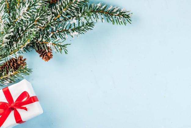 Natal e ano novo 'fundo claro, conceito de cartão, galhos de árvores de natal com pinhas e neve artificial, com caixa de presente, vista superior, cópia espaço