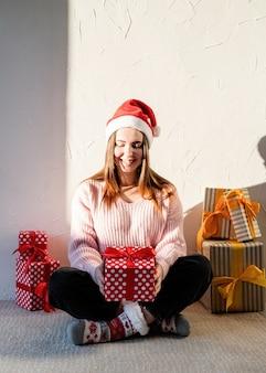 Natal e ano novo jovem com chapéu de papai noel cercada de presentes