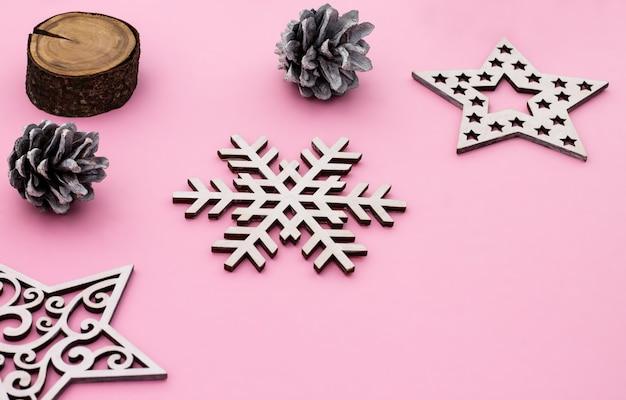 Natal e ano novo. quadro liso rosa leigo com flocos de neve, brinquedos de natal e cones. copie o espaço.