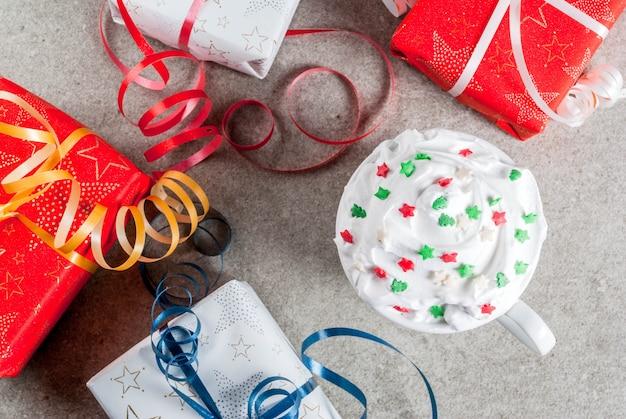 Natal e. caixas de presente de natal e copo para café ou chocolate quente, com chantilly e decoração de estrelas doces, na mesa de pedra cinza, vista superior
