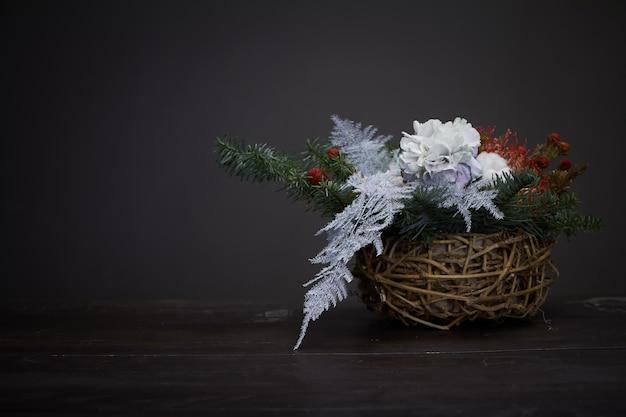 Natal e composição. cesta de vime com galhos de pinheiro decorada com materiais naturais em fundo escuro