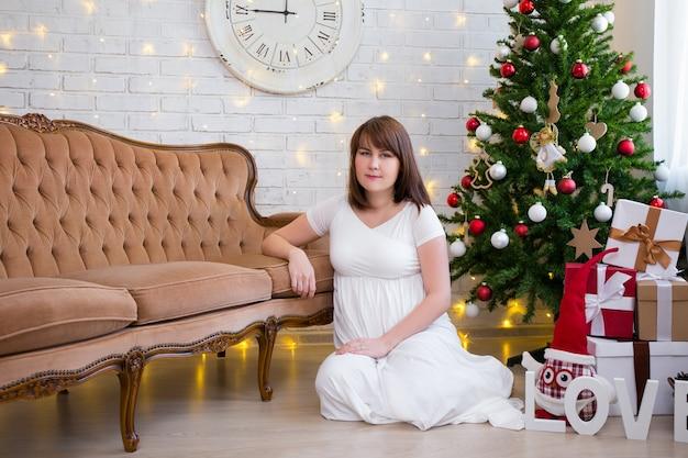 Natal e conceito de família linda mulher grávida em casa com árvore de natal decorada