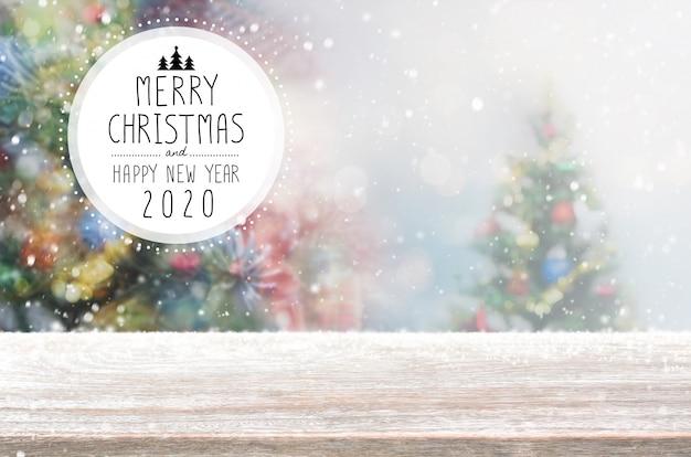 Natal e feliz ano novo 2020 em cima da mesa de madeira vazia no borrão bokeh de fundo de árvore de natal com queda de neve.