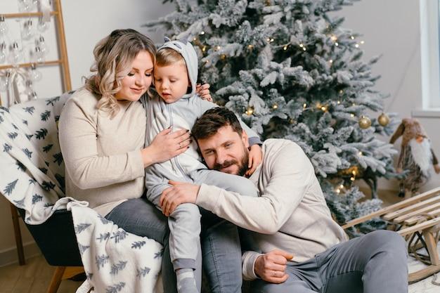 Natal família felicidade retrato de pai, mãe grávida e filho pequeno sentado em uma poltrona em casa perto da árvore de natal abraço sorriso manhã de férias em família jovem adulto europeu