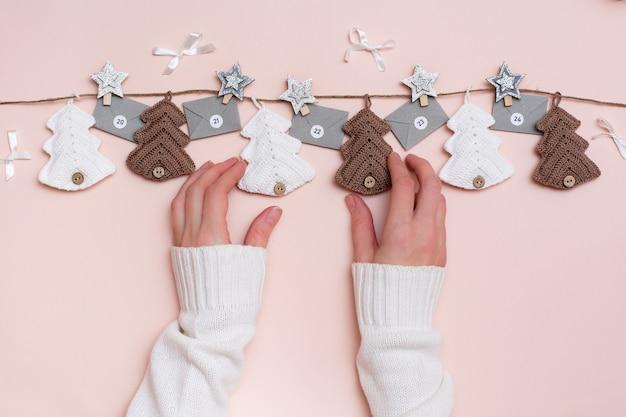 Natal feito à mão. abetos tricotados e calendário do advento em uma linha em uma corda