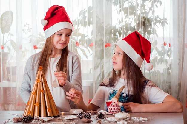 Natal feito à mão. meninas vão decorar uma árvore de natal caseira com brinquedos de madeira