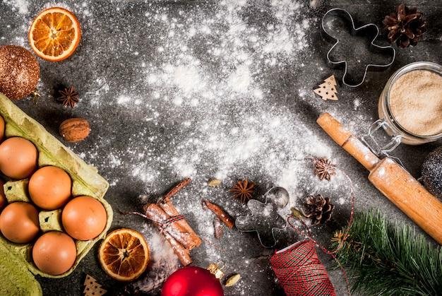Natal, feriado de ano novo de cozinha. ingredientes, especiarias, laranjas secas e formas de cozimento, decorações de natal (bolas, galho de árvore do abeto, cones), na mesa de pedra preta, vista superior copyspace