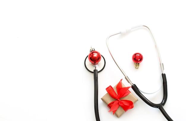 Natal, flatlay médico de ano novo. estetoscópio, presente, decorações de natal em um fundo branco. copie o espaço.