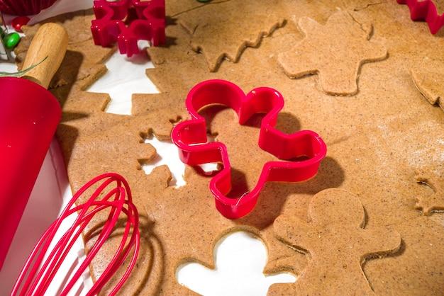 Natal, fundo de cozinha de ano novo. ingredientes de panificação e utensílios - massa de pão de gengibre, cortadores de biscoitos, rolo de massa. fazendo biscoitos doces de natal festivos conceito brilhante festivo vermelho branco