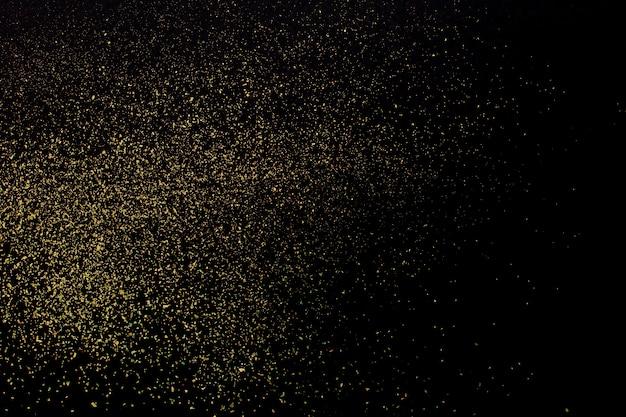 Natal glitter dourados sobre fundo preto. textura abstrata de férias