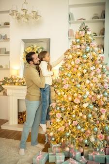Natal. jovem e sua filha decorando uma árvore de natal