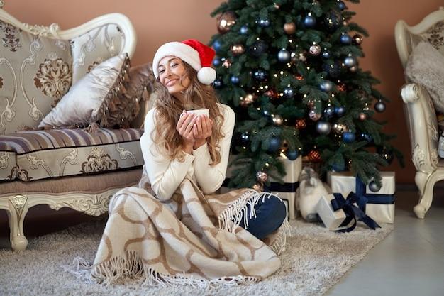 Natal. mulher vestida com chapéu de papai noel de camisola branca e calça jeans sentada no chão perto da árvore de natal com caixa de presente