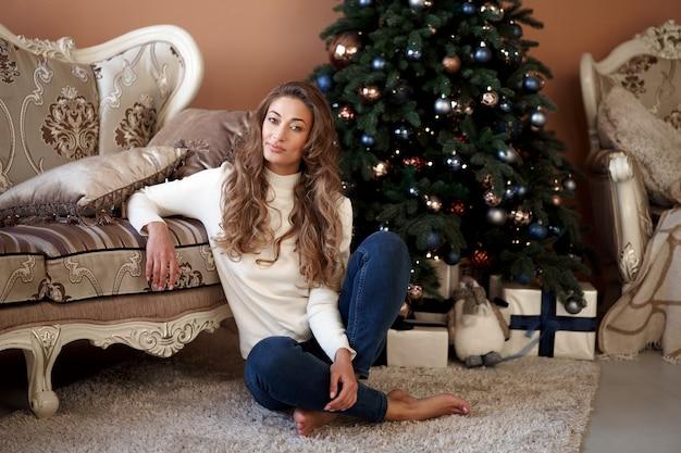 Natal. mulher vestida de suéter branco e calça jeans sentada no chão perto da árvore de natal com uma caixa de presente