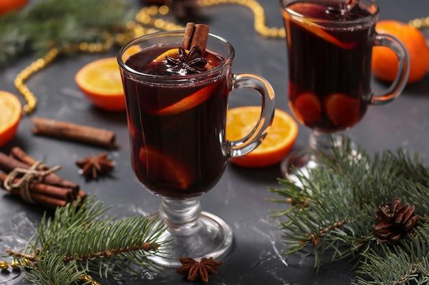 Natal mulled vinho e tangerinas em uma superfície escura, orientação horizontal