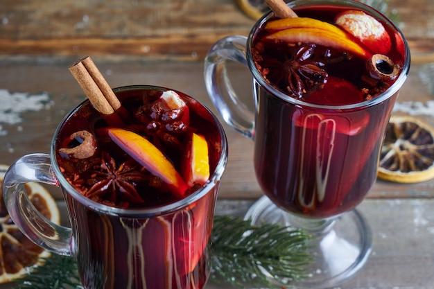 Natal mulled vinho em dois copos com frutas e especiarias na mesa de madeira