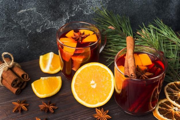 Natal mulled vinho tinto com especiarias e frutas em uma mesa rústica de madeira