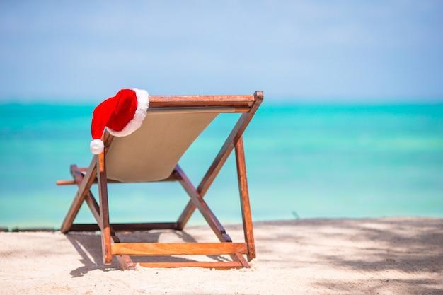 Natal na praia - cadeira com chapéus de papai noel no mar. conceito de férias de natal