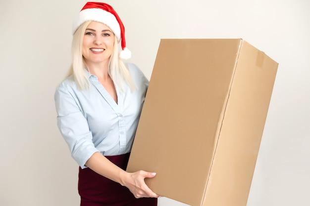 Natal, natal, inverno, conceito de felicidade - mulher sorridente com chapéu de ajudante de papai noel com caixa de pacote