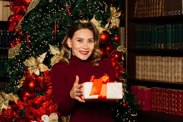 Natal, natal, inverno, conceito de felicidade - mulher sorridente com roupas de papai noel e muitas caixas de presente