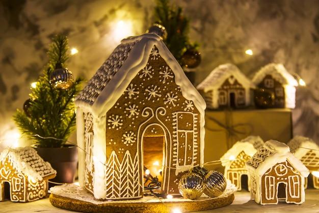 Natal natureza morta com casas de gengibre e guirlanda de luzes no fundo cinza