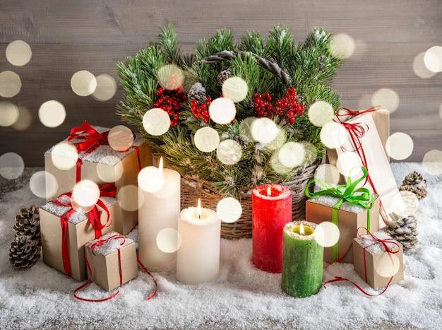 Natal natureza morta com velas acesas e caixa de presente. decoração festiva. imagem de tons de estilo vintage com efeito de luzes