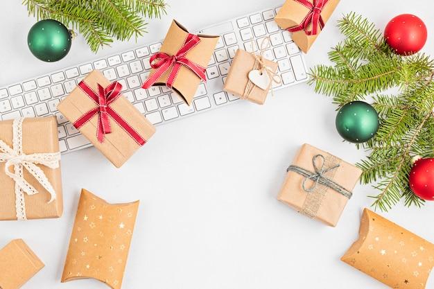 Natal online apresenta conceito de compra com caixas de presente, teclado. vista superior, configuração plana