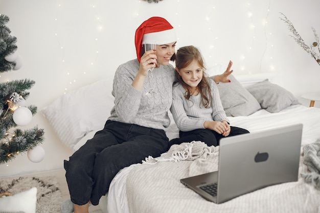 Natal online. comemoração de natal de ano novo na quarentena de bloqueio de coronavírus. festa online. mãe com filha.